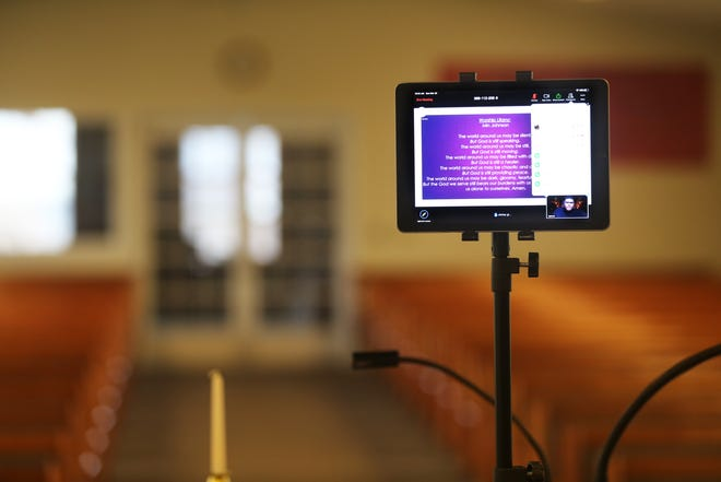A tablet is seen with a backdrop of an empty sanctuary as  associate minister Bryon Johnson appears on a tablet addressing members of  Progressive Baptist Church during a live stream. Churches not only in Milwaukee but across the country were reaching out to their members through social media as a way to continue to connect in light of the coronavirus pandemic.