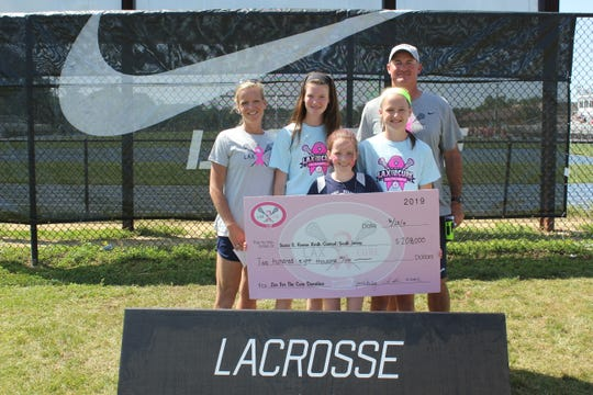 The Shoulberg family, Jessica, Elizabeth, Shea, Gracie and Charlie, presents the Lax for a Cure donation for $208,000 to Susan G. Komen North Jersey.