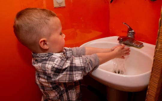 After completing a learning task, Jameson Carter washes his hands at the Young Scholars Preschool located on West Jefferson Pike on Friday, March 20. While some businesses are closing due to the coronavirus, day care centers in Rutherford County are still seeing strong attendance.