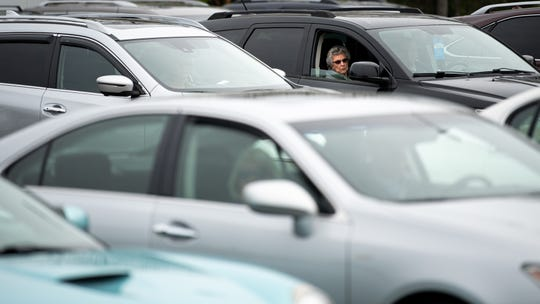 Congregants listen to the service from their parked cars during a parking lot service at Gallatin First Church of the Nazarene in Gallatin, Tenn., Sunday, March 22, 2020. The church hosted the drive-in service in light of the COVID-19 pandemic, allowing congregants to safely watch from their parked cars, listening to the service via radio.