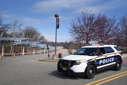 A police officer in a car stands guard in Parking Lot 4 as cones are set up for cars to pass through for testing for Coronavirus at William Paterson University in Wayne on 03/22/20.