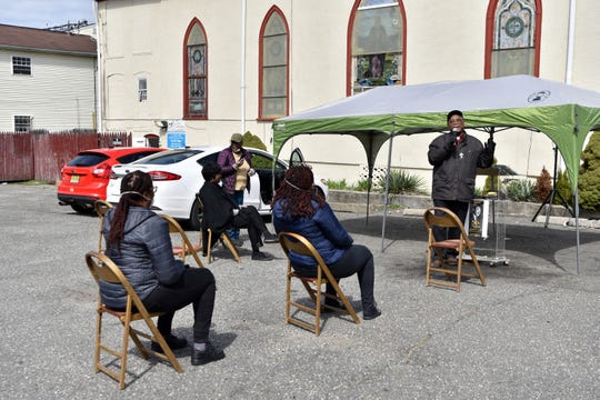 Reverend Allan Boyer of First Bethel AME Church in Paterson conducts a service in the church's parking lot, keeping chairs six feet apart in accordance with social distancing practice recommendations from the CDC to help prevent the spread of the coronavirus on March 22, 2020.