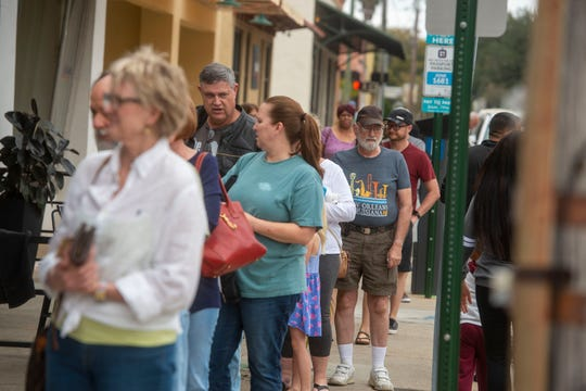 People line up in front of Perfect Plain Brewing Company to buy beer, hand sanitizer or both Sunday, March 22, 2020. In addition to selling beer, they are selling their handmade hand sanitizer for a suggested $5 donation, 100% of the money collected for the hand sanitizer goes to help pay the staff.