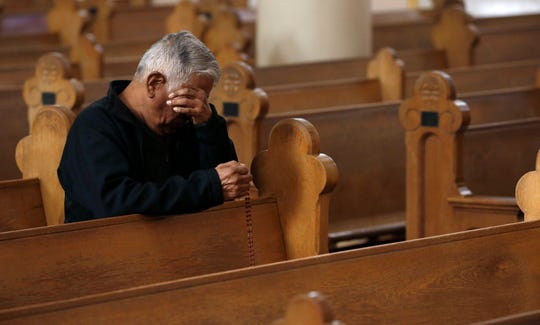 A parishioner wipes away tears during a modest and shortened service Due to the coronavirus, at St. Mary's Roman Catholic Basilica Sunday, March 22, 2020, in Phoenix.
