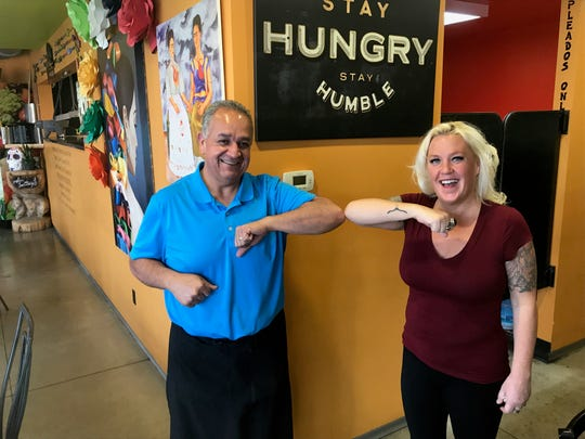"""Jesus """"Chuy"""" Gutierrez, owner of Chuy's Mexican Kitchen, and Jessica Schneider, owner of Junkees Clothing Exchange, bump elbows for a photon Saturday, March 21, 2020."""