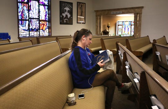 Front office staff member Brucie Ingram cleans prayer books one by one at Our Lady of the Snows Catholic Church in Reno on March 20, 2020. Although all masses are canceled, the church is allowing people to enter and pray from 10am until 2pm Monday through Friday and on Sundays as well.