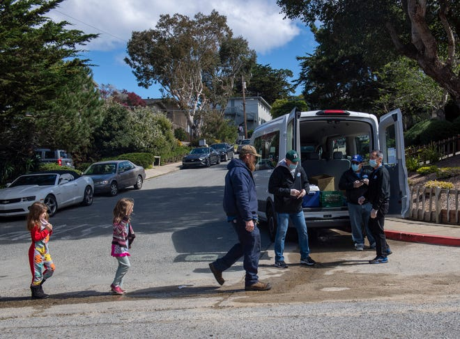 A father walks with his two daughters to get a free lunch and breakfast in Pacific Grove on Friday, March 20, 2020.