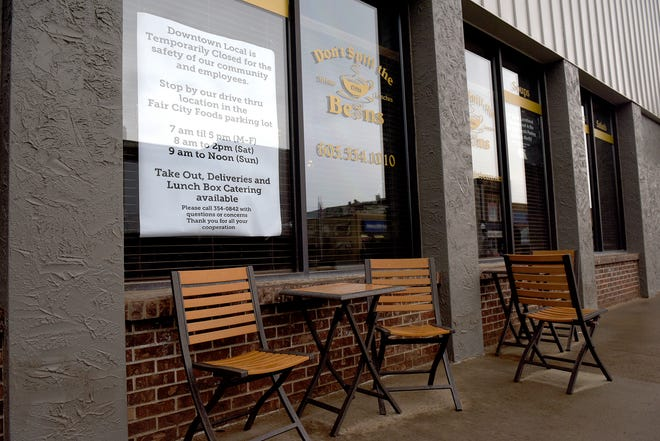 Empty chairs and a closed sign, directing patrons to a different location, outside Don't Spill The Beans coffee shop in Huron Sunday.