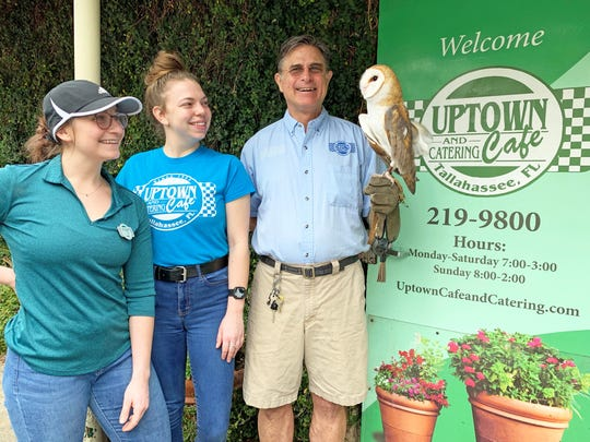 """Fred Tedio, a volunteer with St. Francis Wildlife and co-owner of the Uptown Cafe, recently held his second """"Uptown Cares for St. Francis Wildlife"""" day and donated a portion of all sales made that day. Left to right are Diana, Katie, Fred and Twiggy, a disabled, non-releasable barn owl."""