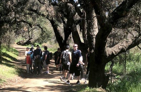 Hikers walk a trail at Malibu Creek State Park on Saturday, March 21, 2020.