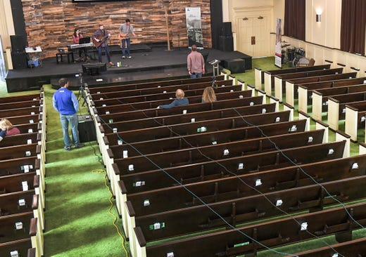 Andrew Cronic stands by the video camera for a live online broadcast of Capstone Church praise band with Lynneth Renberg (keyboard), Adam Renberg (guitar), and Jacob Barfield (bass) during worship in the nearly empty church sanctuary in Anderson, S.C. Sunday, March 22, 2020.