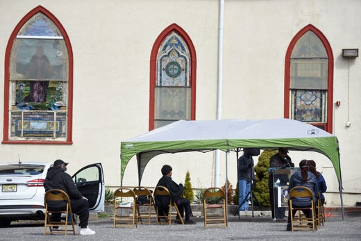 Reverend Allan Boyer of First Bethel AME Church in Paterson, N.J. conducts a service in the church's parking lot, keeping chairs six feet apart in accordance with social distancing practice recommendations from the CDC to help prevent the spread of the coronavirus on March 22, 2020.