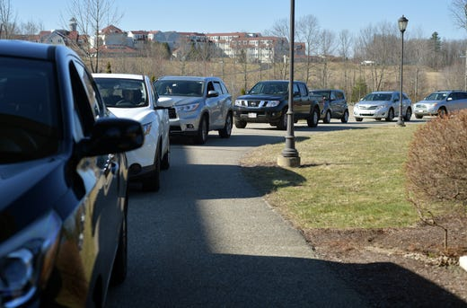 Cars line the entrance to St. Joseph Church.  Parishioners drove to the covered entrance of St. Joseph's Church, walked to the windows with Deacon Bill Shea on the left and and Father Bob Grattaroti on the right, for blessings, on Sunday, March 22, 2020.