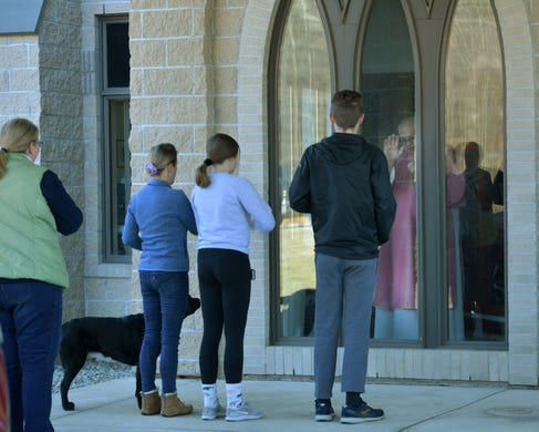 The Humphries family and their dog, are blessed by Deacon Bill Shea.  Parishioners drove to the covered entrance to St. Joseph Church for a blessing on Sunday, March 22, 2020. The parishioners parked their cars and walked up to the windows to receive their blessings.