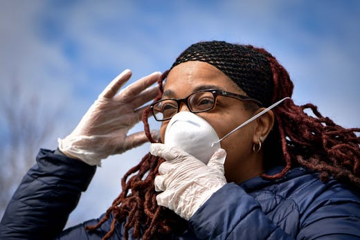 Yvette Bryant-Clanton of Paterson puts on a mask before joining an outdoor worship service at First Bethel AME Church in Paterson on March 22, 2020.