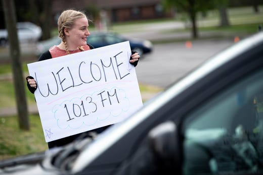 Isabelle Rector, 14, daughter of lead pastor Kevin Rector, welcomes congregants before a parking lot service at Gallatin First Church of the Nazarene in Gallatin, Tenn., Sunday, March 22, 2020. The church hosted the drive-in service in light of the COVID-19 pandemic, allowing congregants to safely watch from their parked cars, listening to the service via radio.