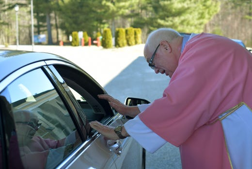 An elderly parishioner is blessed by Deacon Bill Shea on Sunday, March 22, 2020 at the front entrance to St. Joseph Church in Charlton, Mass.