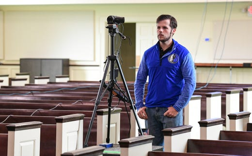 Andrew Cronic stands by the video camera for a live online broadcast of Capstone Church praise band during worship in the nearly empty church sanctuary in Anderson, S.C. Sunday, March 22, 2020.