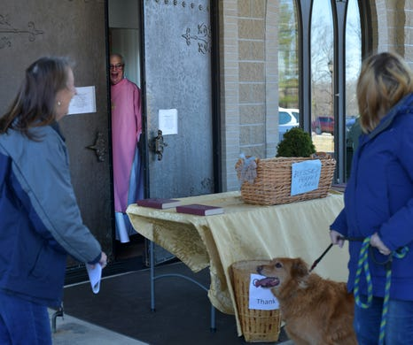 Two women say hello to Deacon Bill Shea on Sunday, March 22, 2020, who peeked out the door, but kept to the social distancing rules at St. Joseph Church in Charlton, Mass.