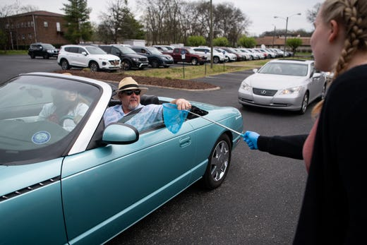 Isabelle Rector, right, 14, daughter of lead pastor Kevin Rector, collects offerings with a butterfly net after a parking lot service at Gallatin First Church of the Nazarene in Gallatin, Tenn., Sunday, March 22, 2020.