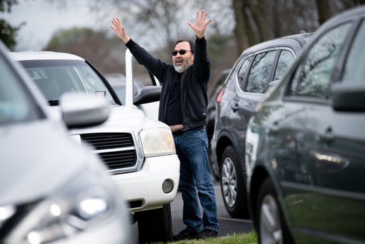 John Bravo, of Gallatin, holds his hands up as music is performed during a parking lot service at Gallatin First Church of the Nazarene in Gallatin, Tenn.