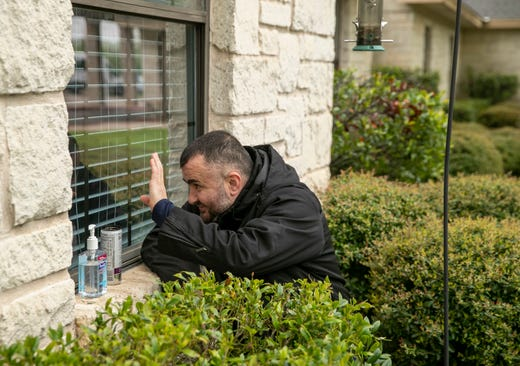 Joze Sola waves through a window to his 70-year-old mother, who lives at a senior citizens center in North Austin, Texas, on March 22, 2020.