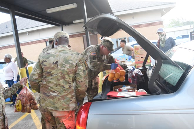 Members of the Louisiana National Guard 527th Engineer Battalion and two other units, 256th Infantry Brigade and the 139th Regional Support Group, help the Food Bank of Central Louisiana with the drive-thru food distribution for the Food Bank's Adopt-a-Senior Program at 3223 Baldwin Avenue on Monday, March 23, 2020. Another distribution date is set for Wednesday, March 25, 2020. This is a no-contact drive-thru distribution and clients are asked to stay in their vehicles and follow the directions of Food Bank staff and security.