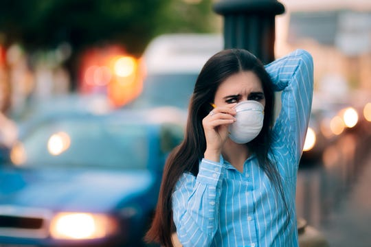 Worried girl fighting urban pollution with safety measures