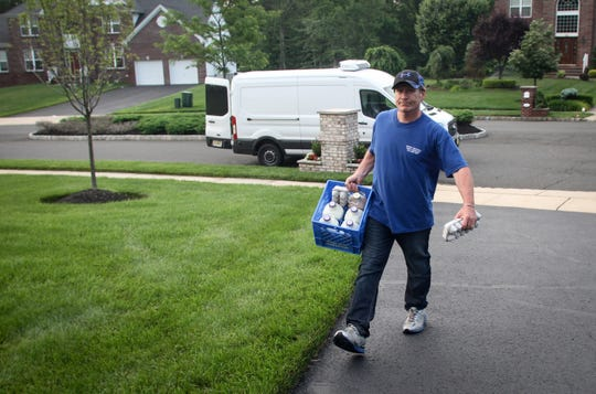 Jeff Milling of Udderly Delicious, a milk delivery service, makes a home delivery in this 2015 photo.