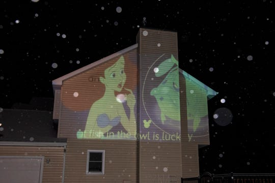 As Michigan practices social distancing, Tom Wood of Battle Creek projects a stream of Disney songs on his house for families to watch from their cars, tuning in on their radios.