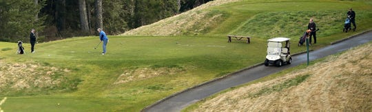 A foursome tees off on the 18th hole of the Olympic Course at Bremerton's Gold Mountain Golf Club on Monday, March 23, 2020.