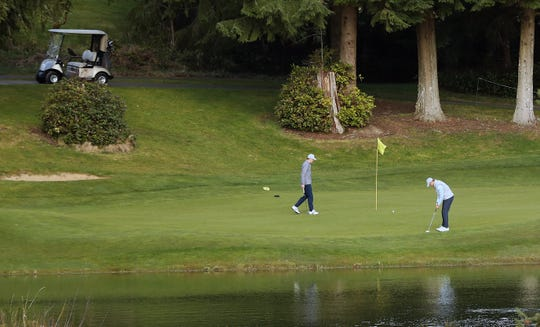 Golfers putt on on the Olympic Course at Bremerton's Gold Mountain Golf Club on Monday, March 23, 2020.