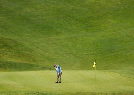 A golfer putts on the 9th hole of the Olympic Course at Bremerton's Gold Mountain Golf Club on Monday, March 23, 2020.