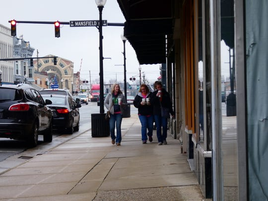 Coffee cups in hand, three women leave the Pelican Coffee House in downtown Bucyrus during the shutdown. The dining room will reopen on May 21.