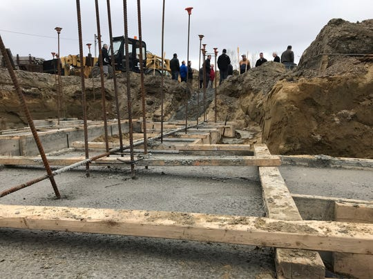 """Groundbreaking: Recently poured foundations are in place for the first building at """"Chittenden Crossing,"""" a development at Five Corners in Essex Junction on March 19, 2020. A belated groundbreaking ceremony is underway in the distance, mostly following social-distancing protocols as a health precaution."""