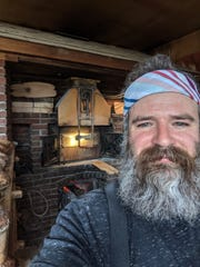 Trent Cooper of Westford stands beside his wood-fired bakery oven on Monday, March 23, 2020. Cooper is donating bread to people who are short of money due to the spread of COVID-19.