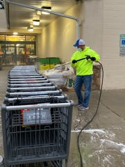 Tom Davis, co-owner of Medford-based Revive Painting & Powerwashing, cleans grocery carts at Murphy's Fresh Markets in Medford. He and James Dalton, the other co-owner of the company, have cleaned the carts  for free at some of the grocery stores in town during the coronavirus pandemic.