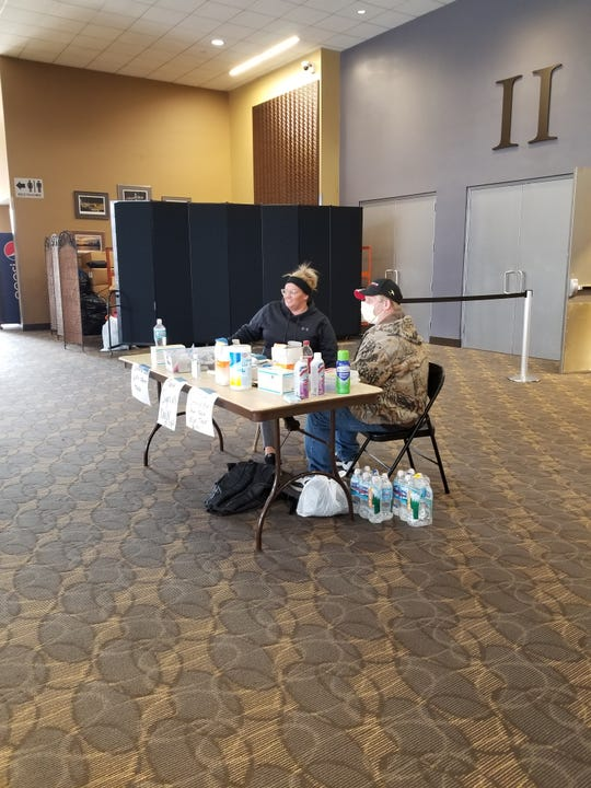 People man a table full of sanitizing items Monday inside the Northern Kentucky Convention Center in Covington, which has been turned into a homeless shelter during the COVID-19 outbreak.