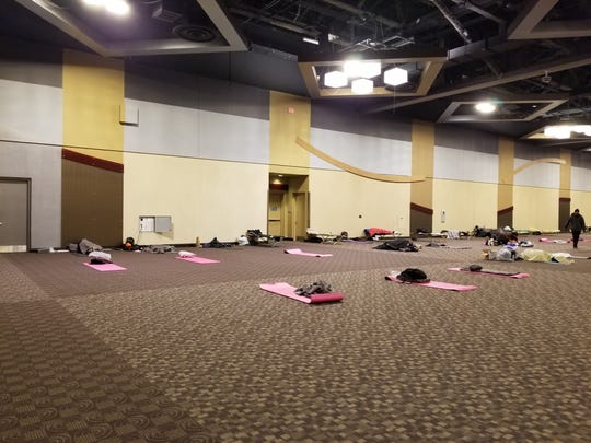 Mats with piles of belongings  are spaced out on the floor  on Monday inside the Northern Kentucky Convention Center in Covington, which has been turned into a homeless shelter during the COVID-19 outbreak.