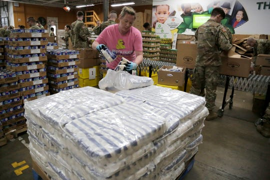 Kathleen Young unpacks bags of rice to be included in supply packages at the Freestore Foodbank Mayerson Distribution Center in the Bond Hill neighborhood of Cincinnati on Monday, March 23, 2020. The Ohio National Guard was deployed to the distribution center on an ongoing mission to pack and distribute food and supplies to those in need.
