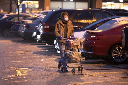 A man makes his way to his car, wearing a mask and gloves during the first hour of shopping at Kroger. The grocery chain is now designating its first hour, 7- 8 am for seniors and at-risk individuals due to the new coronavirus pandemic. A line was already formed before 7 am and the parking filled up quickly, Monday, March 23, 2020.