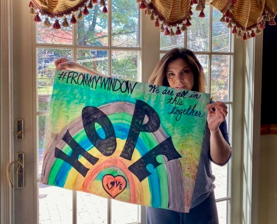 Linden High School Principal Yelena Horré holding artwork to be displayed in her window as part of the district's movement to display uplifting messages for the community.