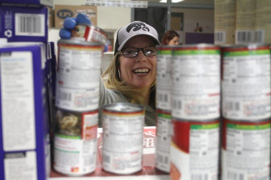 Volunteer Brenda Benge plucks items from the shelves at the Wilder Elementary Food Bank. Volunteers helped distribute groceries from the Wilder Elementary Food Bank on March 23 to vehicles waiting curbside outside the school to maintain social distancing.