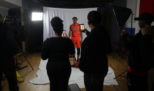 Family members of Benton Harbor's Carlos Johnson take pictures after he was named Michigan Mr. Basketball at the State Champs offices Monday, March 23, 2020.