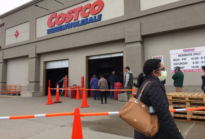 Shoppers wait in line to enter a Costco in Madison Heights on March 23, 2020.