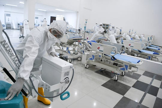 Staff inspect medical equipments at an emergency hospital set up amid the new coronavirus outbreak in Jakarta, Indonesia, Monday. Indonesia has changed towers built to house athletes in the 2018 Asian Games to emergency hospitals with a 3,000-bed capacity in the country's hard-hit capital, where new patients have surged in the past week.