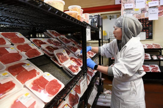 Yoshiro Lee, 30, stocks steaks after he cut them at Bozek's Market in Hamtramck on March 23.