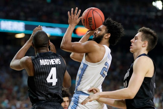 North Carolina's Joel Berry (2) takes a shot between Gonzaga's Jordan Mathews (4) and Zach Collins during the first half in the finals of the 2018 NCAA Final Four. North Carolina defeated Gonzaga 71-65. Berry was named MVP.
