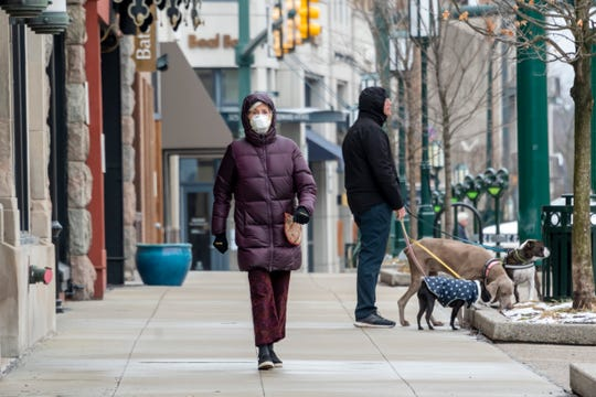 Carol Kozlow wears a mask while taking a walk on Old Woodward in downtown Birmingham on Monday.