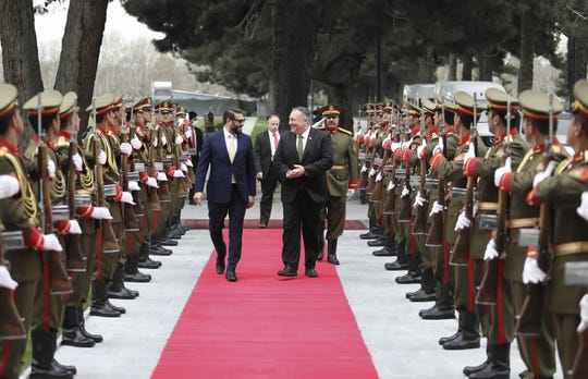 U.S. Secretary of State Mike Pompeo, center right, and Afghan National Security Adviser Hamdullah Mohib, center left, review an honor guard, during an arrival ceremony at the Presidential Palace in Kabul, Afghanistan, Monday, March 23, 2020. Pompeo was in Kabul on an urgent visit Monday to try to move forward a U.S. peace deal signed last month with the Taliban.